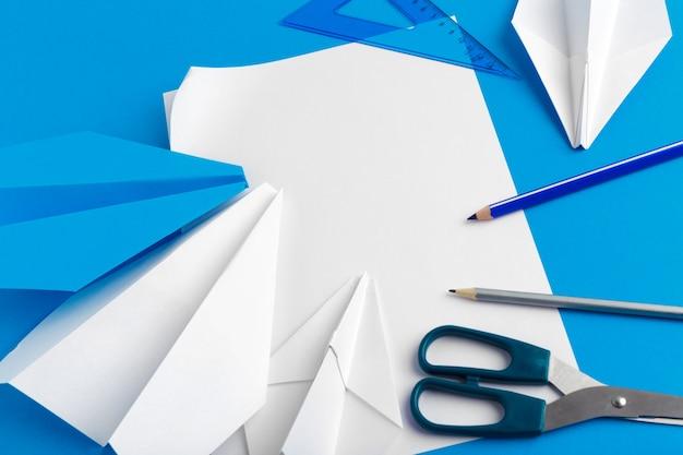 Plat leggen van een papieren vliegtuigje op pastel blauwe kleur achtergrond