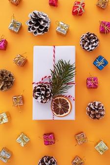 Plat leggen van een wit versierde geschenkdoos en kerstversieringen op oranje