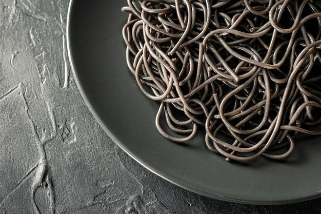 Plat leggen van elegante zwarte plaat van pasta met sepia inkt met zwarte gestructureerde achtergrond