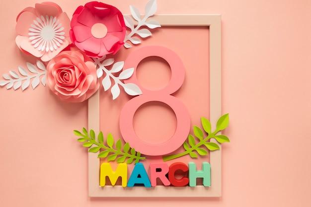 Plat leggen van frame met datum en papieren bloemen voor vrouwendag