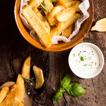 Plat leggen van frietjes in kom met speciale saus en kruiden