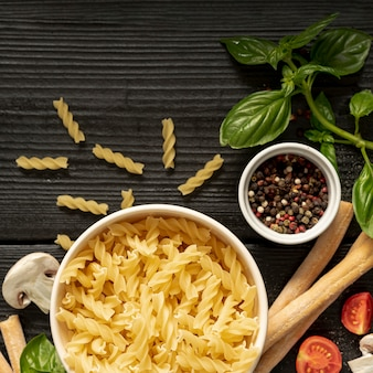 Plat leggen van fusilli pasta peper en grissini op houten tafel
