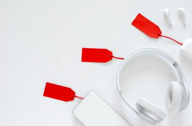 Plat leggen van gadget met rood prijskaartje op witte achtergrond voor online de verkoopconcept van cyber monday.