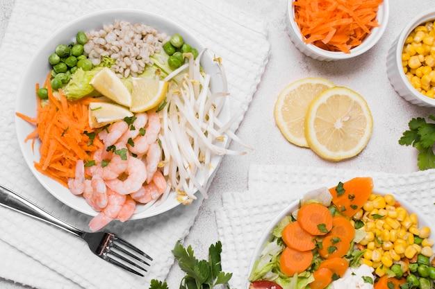 Plat leggen van garnalen en groenten op borden