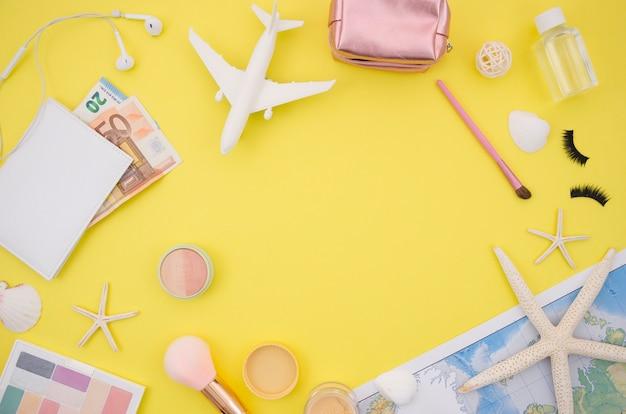 Plat leggen van gele achtergrond met reisaccessoires