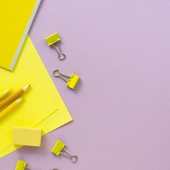 Plat leggen van gele en lila schoolbenodigdheden
