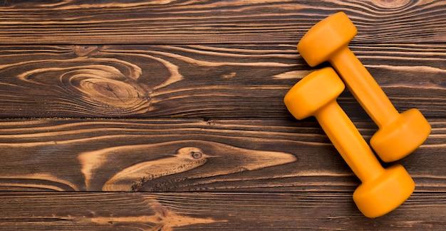 Plat leggen van gele gewichten op houten achtergrond en kopie ruimte