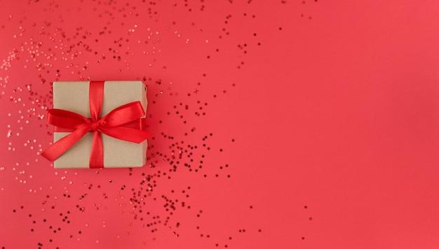 Plat leggen van geschenkdoos verpakt in ambachtelijk papier met rood lint met confetti op rood