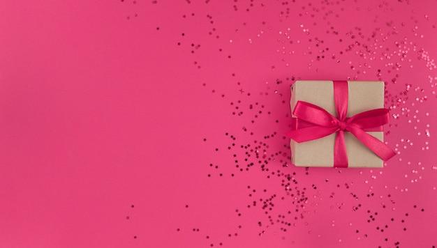 Plat leggen van geschenkdoos verpakt in ambachtelijk papier met rood lint met confetti op roze,