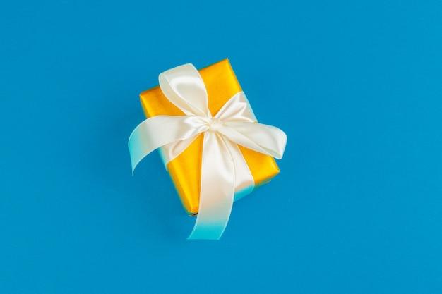Plat leggen van geschenkdoos versierd met strik op blauwe achtergrond