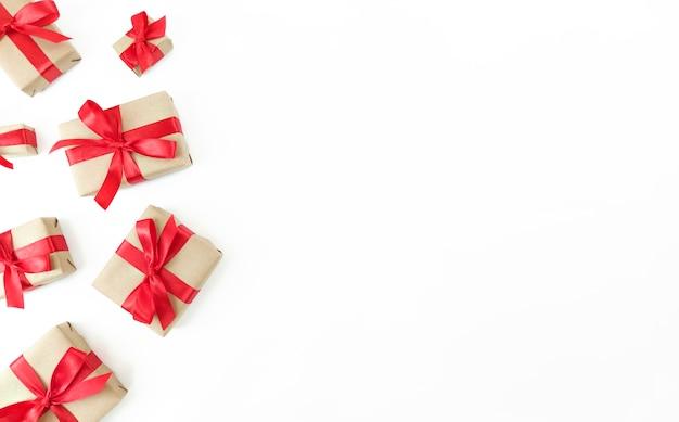 Plat leggen van geschenkdozen met rode linten op wit