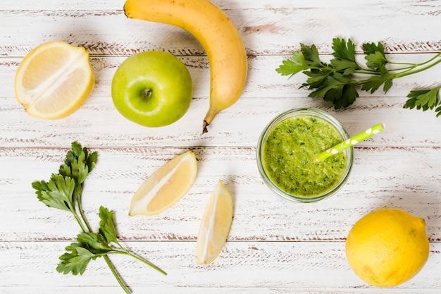 Plat leggen van glas gezonde smoothie met appel en banaan