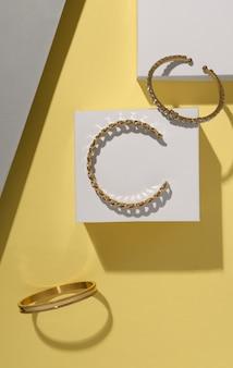 Plat leggen van gouden armbanden op witte blokjes op gele achtergrond