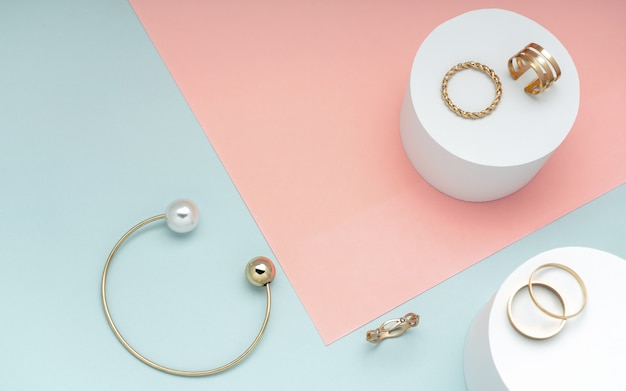 Plat leggen van gouden en parel armband en gouden ringen collectie op roze en groen papier achtergrond