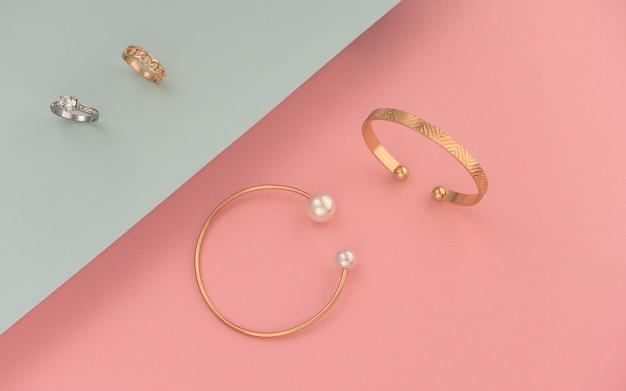 Plat leggen van gouden en zilveren ringen en armbanden op roze en blauw