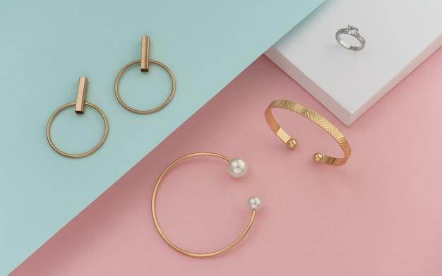 Plat leggen van gouden jewelries op pastel kleuren papier achtergrond