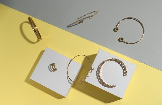Plat leggen van gouden sieraden op grijs en geel met kopie ruimte