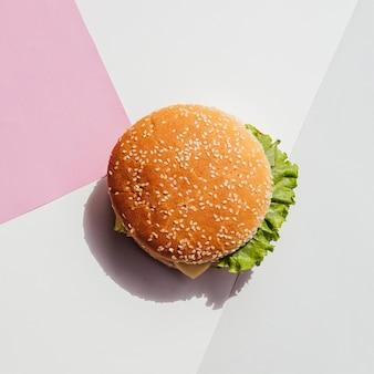 Plat leggen van hamburger op eenvoudige achtergrond