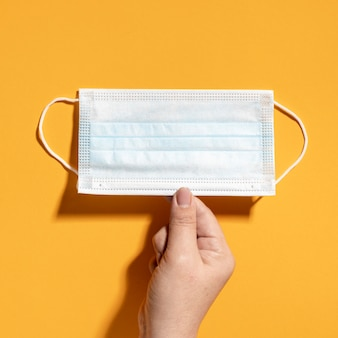 Plat leggen van hand met medische masker