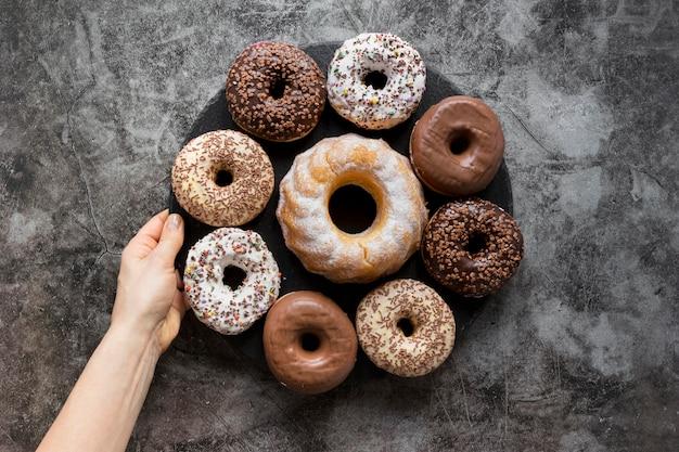 Plat leggen van hand met plaat van donuts