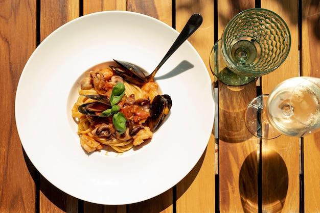 Plat leggen van heerlijke pasta op houten tafel Gratis Foto