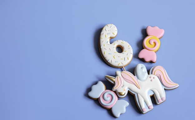 Plat leggen van helder geglazuurde peperkoekkoekjes in de vorm van snoep op een blauwe achtergrond.