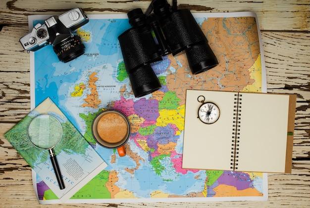 Plat leggen van het reisplanningsconcept. bovenaanzicht van een dagboek, een verrekijker, een kompas, een retro fotocamera, een koffie en een kaart van europa op een witte houten tafel