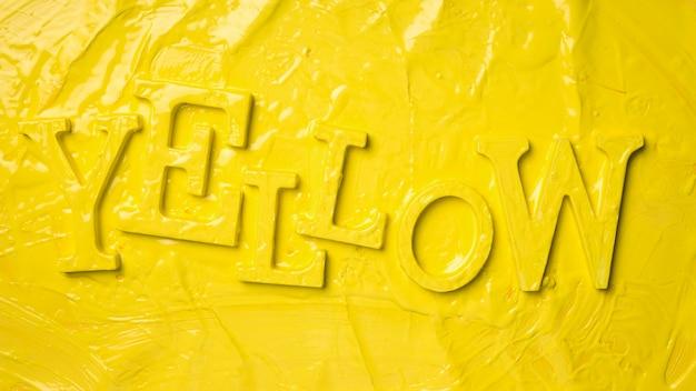 Plat leggen van het woord geel met verf