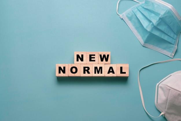 Plat leggen van houten blokblokjes voor nieuwe normale bewoordingen met chirurgisch masker