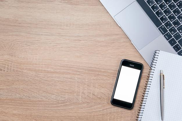 Plat leggen van houten bureau met laptop, pen en notitieboekje met kopie ruimte achtergrond.