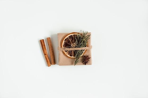 Plat leggen van kerst ambachtelijke geschenkdoos. handgemaakte bruine papieren doos met kerstboomtak en kaneelstokjes en droge sinaasappel.