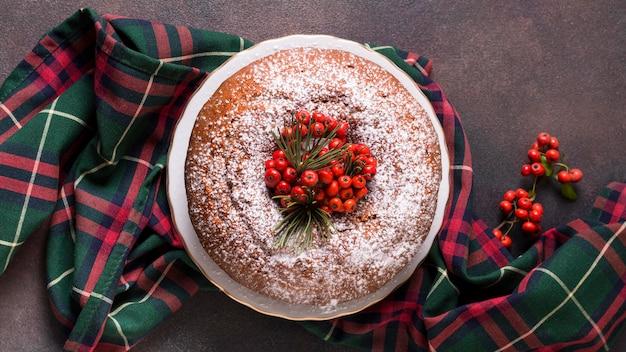 Plat leggen van kerst cake met rode bessen