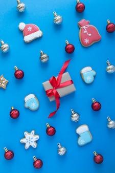 Plat leggen van kerst peperkoek en geschenkdoos op de blauwe achtergrond. bovenaanzicht. locatie verticaal.