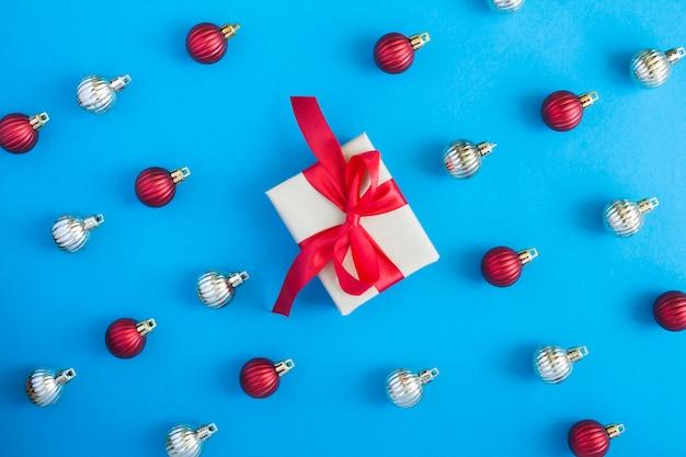 Plat leggen van kerstballen en geschenkdoos op de blauwe achtergrond. bovenaanzicht. detailopname.