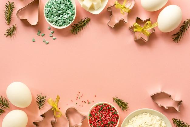 Plat leggen van kerstkoekjessnijders en bakselingrediënten op een roze achtergrond. ruimte voor tekst.
