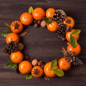 Plat leggen van kerstkrans maken van mandarijnen en dennenappels