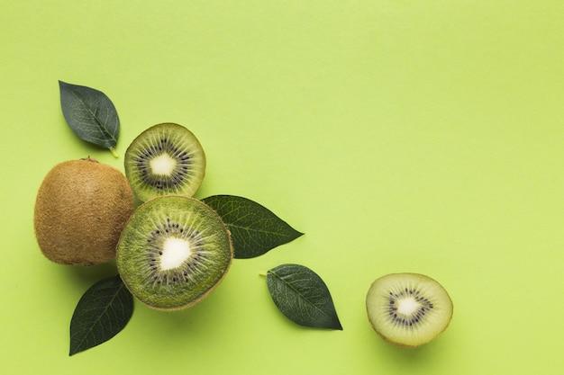 Plat leggen van kiwi en bladeren met kopie ruimte