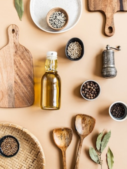 Plat leggen van kleine kommen verschillende droge kruiden, houten keukengerei, olijfolie in glazen fles