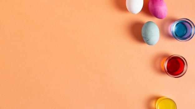 Plat leggen van kleurrijk beschilderde paaseieren met kleurstof en kopie ruimte