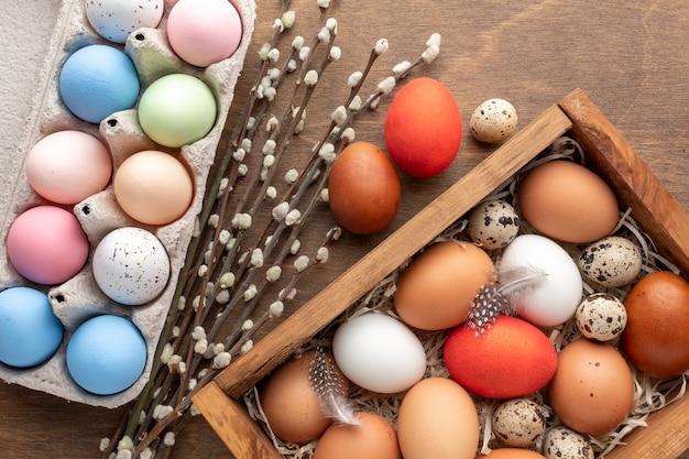 Plat leggen van kleurrijke eieren voor pasen in doos en karton met bloemen