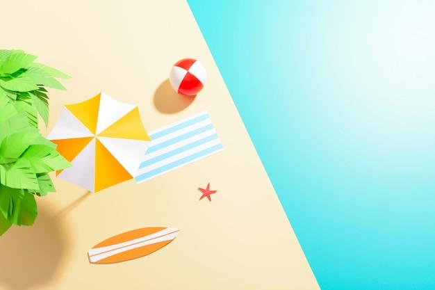 Plat leggen van kleurrijke paraplu op strand met groene boom en vermakelijk object op veelkleurige ondergrond.