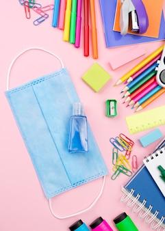 Plat leggen van kleurrijke terug naar school briefpapier met medische masker