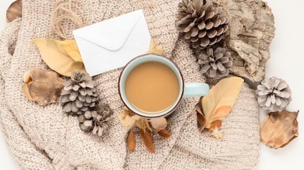 Plat leggen van koffiemok met dennenappels en herfstbladeren