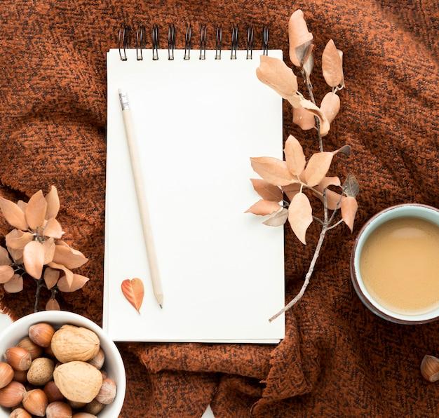 Plat leggen van koffiemok met herfstbladeren en notebook