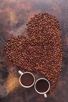 Plat leggen van kopje koffie en koffiebonen gegoten in de vorm van een hart