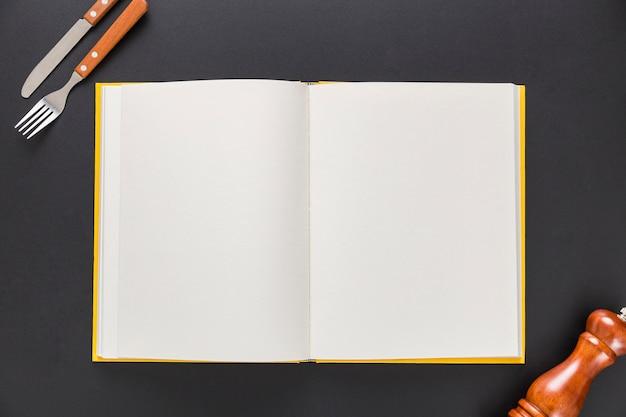 Plat leggen van leeg menuboek met bestek