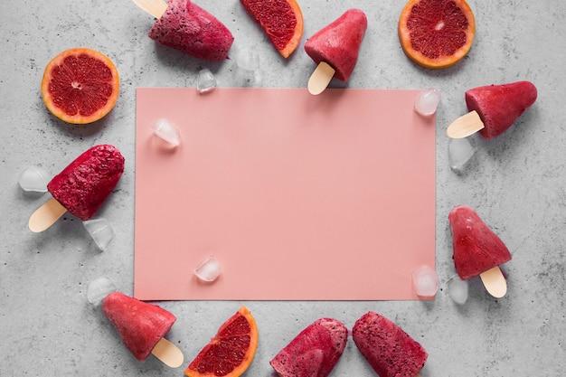 Plat leggen van lekkere ijslollys met rode grapefruit en kopieer de ruimte
