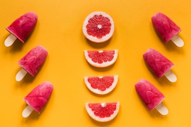 Plat leggen van lekkere ijslollys met rode grapefruit
