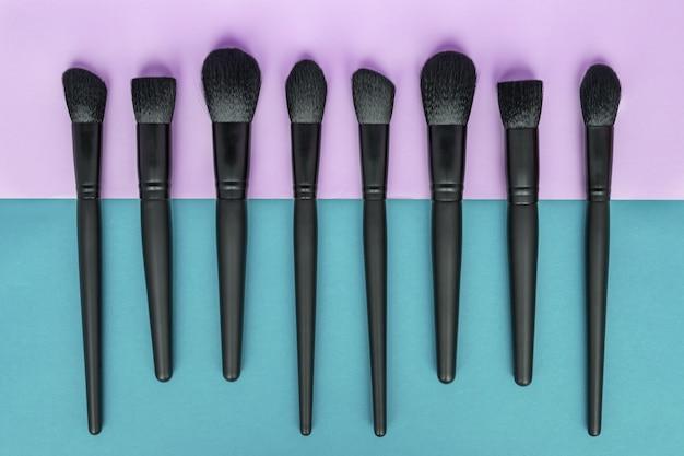 Plat leggen van make-up borstels collectie op kleurrijke ruimte.