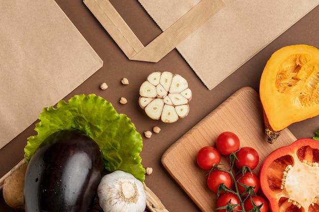Plat leggen van mand met biologische groenten met papieren zak